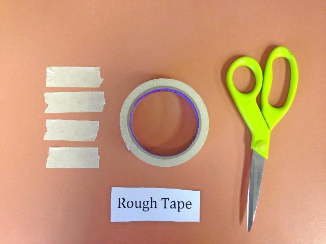Figure 2.Cuatro pedazos de cinta adhesiva de superficie rugosa cortadas para que igualen la altura de la pared del recipiente pequeño.