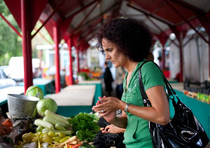 Figure 1.A consumer peruses produce available at a farmers market.