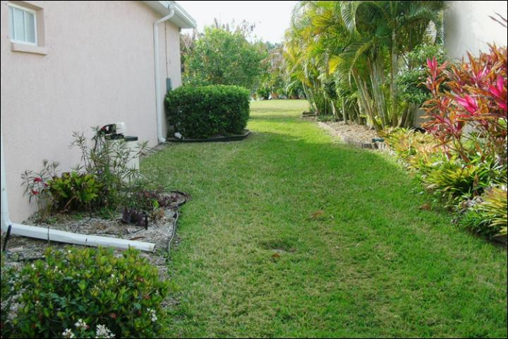 Figure 12.BEFORE -- March 2009. A typical side-yard in a traditional development landscape in Osprey, Fla.. The landscape includes a large area of sod and exposed gutters and utilities.