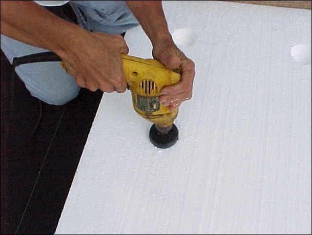 Figure 4.Drilling holes in styrofoam for transplants.